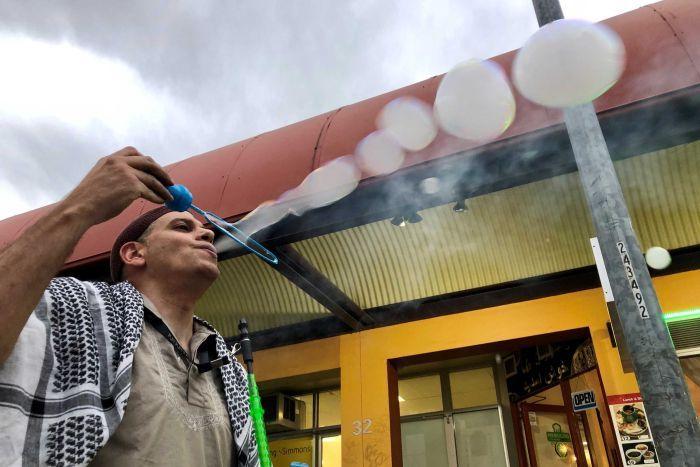 Whale Eade tient une baguette à bulles dans la main alors qu'il souffle des bulles de fumée. Il peut être vu d'en bas, avec un ciel gris au-dessus.